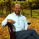 Winemaker Eric Miller in vineyard with glass of wine.